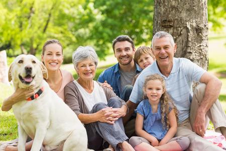 familien: Portrait einer Gro�familie mit ihrem Haustier Hund sitzt im Park