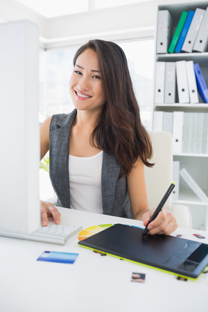 casuals: Portrait of a smiling casual female photo editor using graphics tablet in a bright office