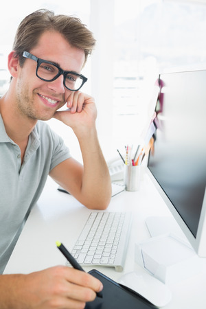 graphics tablet: Side view of a casual male photo editor using graphics tablet in a bright office Stock Photo