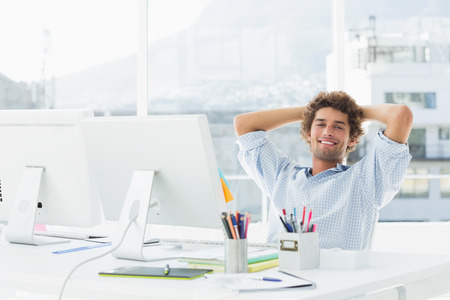 Portrait of a relaxed casual young business man with computer in a bright office