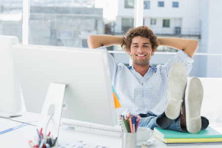 work desk: Relaxed casual young business man with legs on desk in a bright office Stock Photo