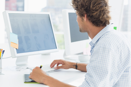 design graphic: Side view of a male artist drawing something on graphic tablet with pen
