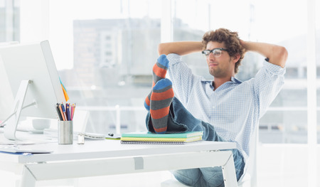 casual: Relaxed casual young business man with legs on desk in a bright office Stock Photo