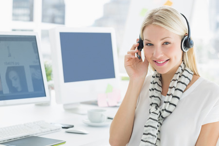 Close-up of a smiling casual young woman with headset sitting by computers in a bright office photo