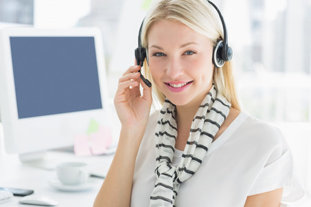 Portrait of a smiling casual young woman with headset sitting by computer in a bright office photo
