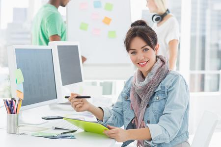 Retrato de un artista a dibujar algo en la tableta gráfica con los colegas detrás en la oficina