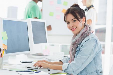 robo: Vista lateral retrato de un artista que usa el ordenador con los colegas detr�s en la oficina Foto de archivo