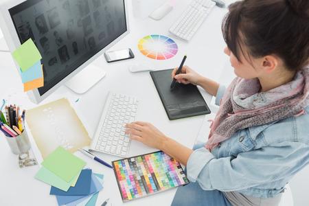 graphics: Vista de �ngulo alto de un artista dibujar algo en la tableta gr�fica en la oficina