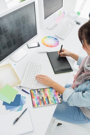 작가가 사무실에서 그래픽 태블릿에 뭔가를 그리기의 높은 각도보기