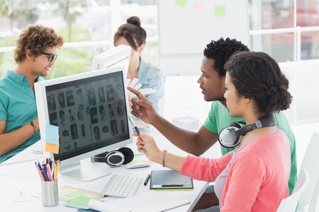 designer: Group of casual young men and women working on computers in a bright office Stock Photo