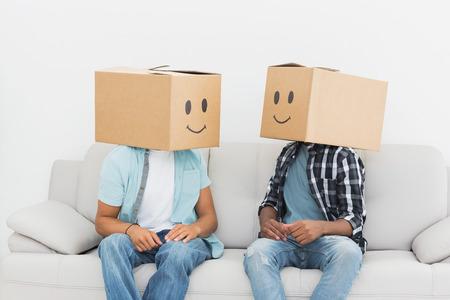 smiley content: Hommes avec des bo�tes plus souriants heureux visages alors qu'il �tait assis sur le canap� Banque d'images