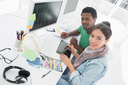 컴퓨터 그래픽: 동료가 사무실에서 그래픽 태블릿에 무언가를 그리기 예술가의 높은 각도 초상화