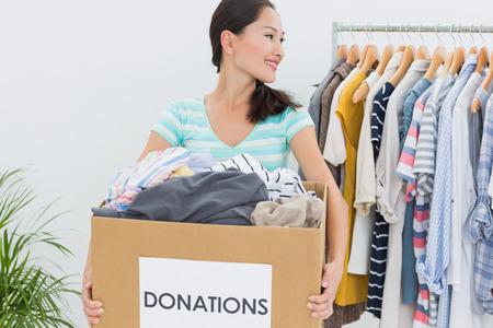 Glimlachende jonge vrouw met kleren donatie