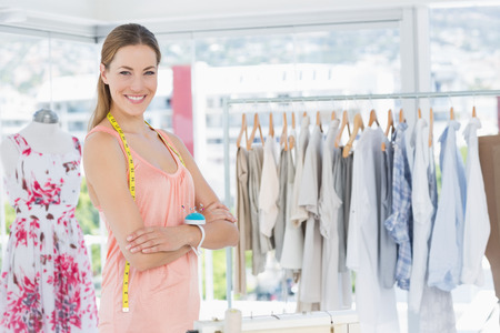 Portrait of a beautiful female fashion designer with rack of clothes in the store photo