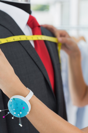 bespoke: Extreme close-up of a female fashion designer measuring suit on dummy at office