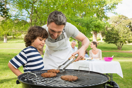 Man and son barbecuing with family in the background at park Stock Photo