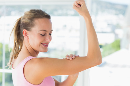 toning: Side view of a young woman flexing muscles in the gym