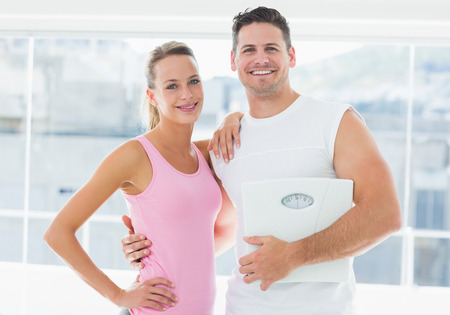 Portrait of a fit couple holding weighing scale in bright exercise room photo
