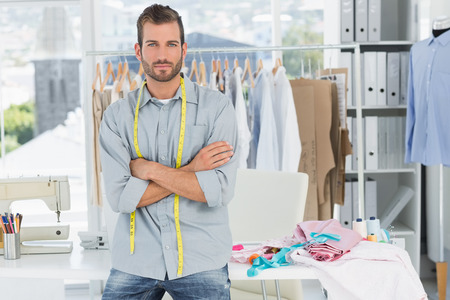 Portrait of a handsome male fashion designer with arms crossed in the studio photo