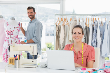 Young woman using laptop with male fashion designer working in background at the studio photo