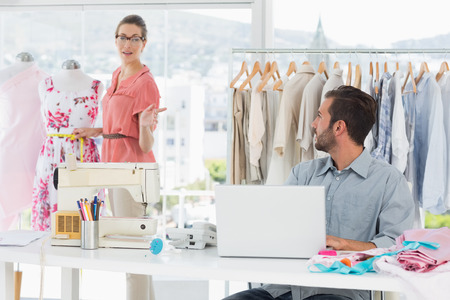 Young man using laptop with female fashion designer working in background at the studio photo