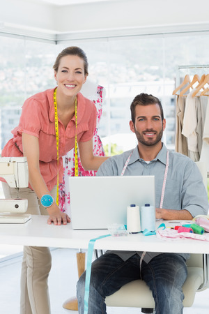 Male and female fashion designers with laptop at work in a bright studio photo