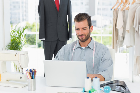 Young male fashion designer using laptop in the studio photo