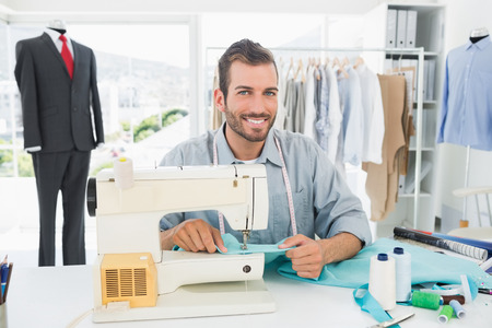 Portrait of a smiling male tailor sewing in workshop Stock Photo