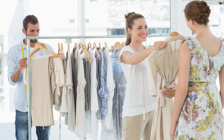 suggesting: Female seller helping shopper choose the clothes in the store