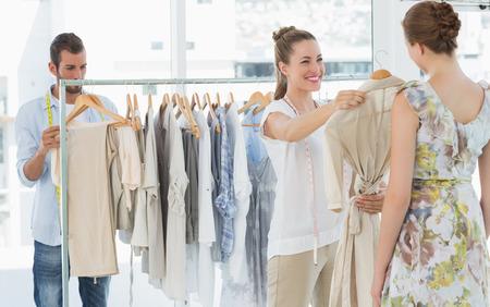 Weiblich Verkäufer helfen Shopper wählen Sie die Kleidung im Laden