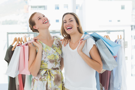 Portrait of two cheerful young women with shopping bags in the clothes store photo