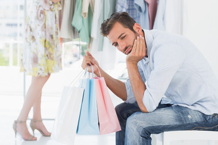 Bored man sitting with shopping bags while woman by clothes rack in the background photo