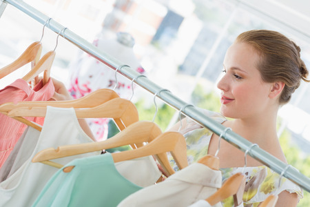 Close-up of a smiling female customer selecting clothes at clothing rack in store photo
