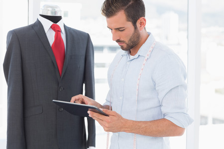 Concentrated young male fashion designer looking at digital tablet by suit on dummy in the studio photo