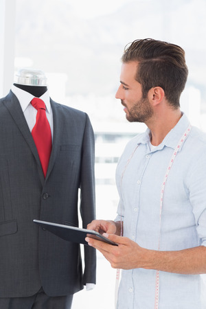 Concentrated young male fashion designer with digital tablet looking at suit on dummy in the studio Stock Photo - 27073801