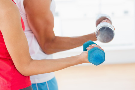 Closeup mid section of a sporty young couple with dumbbells in the gym photo