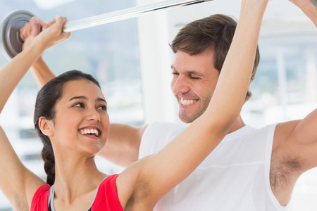Happy male trainer helping young fit woman to lift the barbell in the gym photo