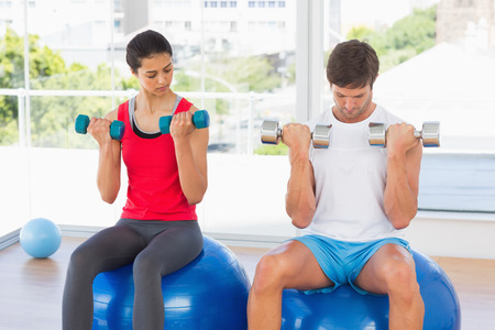 Man and woman lifting dumbbell weights while sitting on fitness balls in a bright gym photo