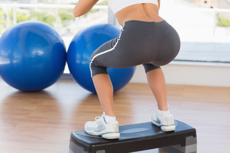 Low section rear view of a fit young woman exercising on step in gym photo