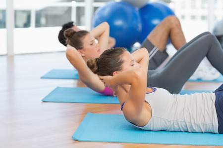 Side view of three determined young people doing sit ups in the fitness studio photo