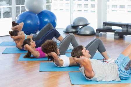Side view of determined young people doing sit ups in the fitness studio photo