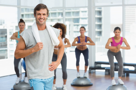 Portrait of a smiling man with fit people performing step aerobics exercise in gym photo