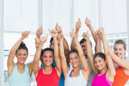 Portrait of fit young people gesturing thumbs up in a bright exercise room photo