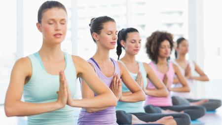 manos unidas: Las mujeres j�venes deportivo con las manos juntas sentado en la fila en un gimnasio brillante