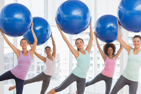 Happy fitness class and instructor doing pilates exercise with fitness balls in bright room Banco de Imagens