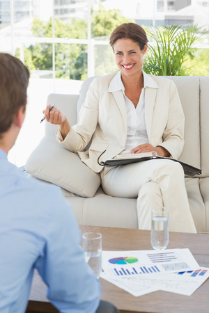 Businesswoman smiling at colleague sitting on sofa in the office photo