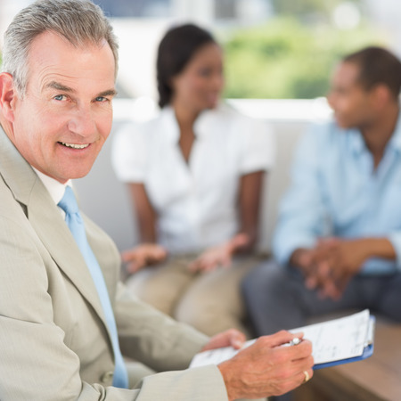 Salesman smiling at camera with couple behind him in the office photo
