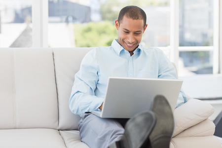Happy businessman using laptop with his feet up in the office photo