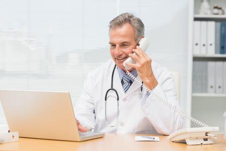 landline: Medico con laptop e parlando al telefono alla scrivania nel suo ufficio presso l'ospedale