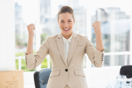 clenching fists: Portrait of a cheerful young businesswoman clenching fists in a bright office